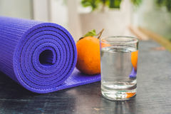 Yoga mat, water, orange and mango on a wooden background. Equipment for yoga. Concept healthy lifestyle, diet and sport. Copy spac Royalty Free Stock Image