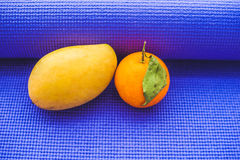 Yoga mat, water, orange and mango on a wooden background. Equipment for yoga. Concept healthy lifestyle, diet and sport. Copy spac Royalty Free Stock Images