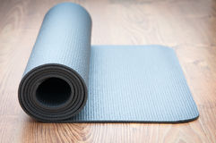 Yoga mat. On wooden background Royalty Free Stock Image