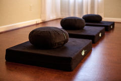 Yoga mats in a line. A group of yoga mats and pillows in a line at a yoga studio Stock Photography