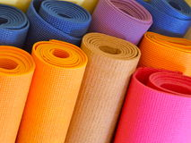 Yoga mats. Several colorful yoga mats leaning on a wall Royalty Free Stock Images