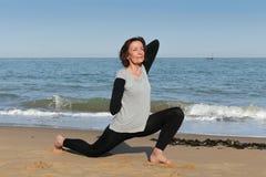 Yoga matura della cobra del bambino della donna sulla spiaggia Fotografie Stock Libere da Diritti
