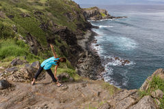 Yoga on Maui. A woman practicing yoga along the rugged Maui coast Royalty Free Stock Images