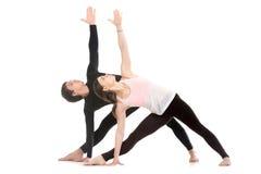 Yoga med partnern, den fördjupade triangeln poserar Royaltyfri Foto