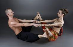 Yoga med partnern Instruktörshow en av asanas Arkivbild