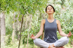 Yoga and meditation. Young woman in green forest, yoga and meditation Royalty Free Stock Photography