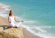 Yoga meditation. Young attractive brunette sitting in lotus position on the beach Royalty Free Stock Photo
