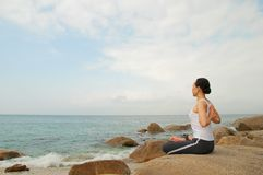 Yoga meditation. Young Woman Exercising Yoga meditation in the rocky beach Royalty Free Stock Image