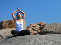 Yoga meditation. Young Woman Exercising Yoga meditation on the Rock Royalty Free Stock Photography
