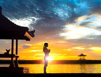 Yoga Meditation at Beach in Bali. Silhouette of young woman practising yoga meditation in standing full lotus position near gazebo or pagoda at beach in Bali vector illustration