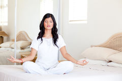 Yoga meditation on bed. Beautiful young woman practicing yoga meditation on her bed Stock Photography