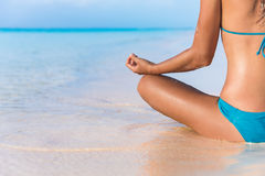 Yoga meditation bikini woman meditating on beach. Yoga meditation on beach. Bikini body woman meditating relaxing sitting in water in tropical summer travel Stock Photos
