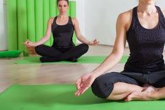 Yoga meditation class. Girls in yoga lotus position in studio Royalty Free Stock Photos