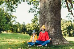 Yoga and meditation concept. Beautiful young woman in knitted clothes and small child keep eyes closed, meditate outdoors in green royalty free stock photo