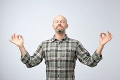 Yoga and meditation concept. Handsome bald man with bristle keeping eyes closed while meditating. Feeling relaxed, calm, peaceful holding hands in mudra sign royalty free stock images