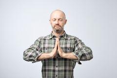 Yoga and meditation concept. Handsome bald man with bristle keeping eyes closed while meditating. Feeling relaxed, calm, peaceful holding hands in mudra sign stock image