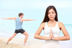 Yoga meditation couple. Meditating outdoor on beach. Young happy interracial couple during outdoor workout. Beautiful young Asian fitness women and Caucasian Stock Photography