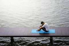 Yoga meditation exercise by top view. Top view photo of healthy man doing Yoga meditation exercise on wooden bridge above water pond. Healthcare and Fitness Royalty Free Stock Photography