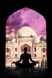 Yoga meditation in India. Yoga meditation in lotus pose by man silhouette in arch at Humayuns tomb and purple sky background in New Delhi, India stock images