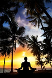 Yoga meditation in India. Yoga meditation silhouette by man at palms, ocean and sunset sky background in India stock images