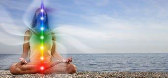 Free Yoga Meditation Outdoors. Glowing Seven All Chakra. Woman Sits In A Upward Salute Pose On Beach Sunset View, Kundalini Energy. Stock Image - 225022521