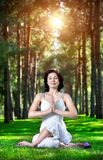 Yoga meditation in park. Yoga meditation in gomukhasana pose by woman in white costume on green grass in the park around pine trees Stock Photos