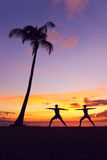 Yoga meditation people meditating warrior pose. Yoga meditation people meditating training warrior pose outside by beach at sunrise or sunset. Woman and men yoga royalty free stock photo