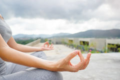 Yoga and meditation on rooftop. Closeup of young woman in lotus pose on roof with city and mountains view Stock Image