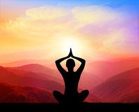 Yoga and meditation. Silhouette of man on the mountain. Dawn in the mountains Stock Photography