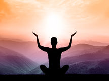 Yoga and meditation. Silhouette of man on the mountain. Royalty Free Stock Images