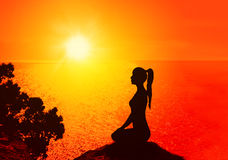 Yoga and meditation. Silhouette of a woman on the beach at sunrise.Yoga and meditation Royalty Free Stock Photography