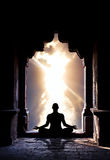 Yoga meditation in temple. Yoga meditation in lotus pose by man silhouette in old temple arch at dramatic sky background. Free space for text stock photography