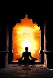 Yoga meditation in temple. Yoga meditation in lotus pose by man silhouette in old temple arch at orange sunset sky background. Free space for text royalty free stock images