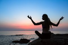 Yoga meditation woman silhouette on the Sea. During amazing sunset Royalty Free Stock Photo