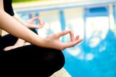 Yoga-Meditationshand durch Pool Stockfotografie