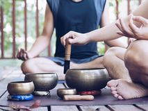Two yoga men do yoga outdoor with singing bowls royalty free stock photo