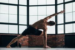 Yoga men sport lifestyle strong toned fit muscles. Yoga for men. sport fitness and athletic lifestyle. strong body and toned muscles. man exercising asana in gym royalty free stock image