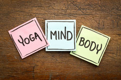 Yoga, mind, and body word abstract. Handwriting in black ink on sticky notes against rustic wood stock photos