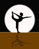 Yoga In The Moonlight. Silhouette of female in full moonlight in a King Dancer Yoga stance Stock Photo