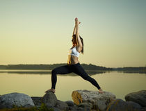 Yoga in the morning. The beautiful young woman exercise yoga early at morning, calm sea on background Royalty Free Stock Photos