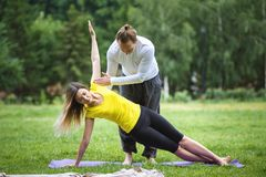 Yoga in morning park - instructor is training young women for flexibility. Telephoto Stock Photo