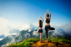 Yoga. Mother and daughter doing yoga at top of mountain Royalty Free Stock Photography
