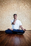 Yoga nadi suddhi pranayama. Handsome Indian man in white shirt doing nadi suddhi pranayama in padmasana position with Vishnu mudra gesture indoors on wooden royalty free stock photography