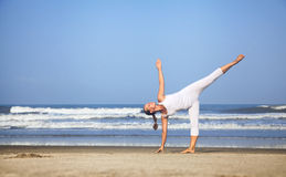 Yoga near the ocean in India. Yoga half-moon pose by woman in white costume on the beach near the ocean in India Royalty Free Stock Image
