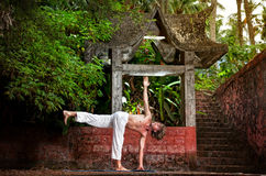 Yoga near temple. Yoga parivrtta ardha chandrasana revolved half moon pose by man in white trousers near stone temple at sunset background in tropical forest Royalty Free Stock Image