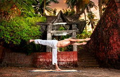 Yoga near temple. Yoga virabhadrasana warrior III pose by man in white trousers near stone temple at sunset background in tropical forest Stock Images