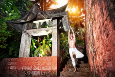 Yoga near temple. Yoga vrikshasana tree pose by man in white trousers near stone temple at sunset background in tropical forest Royalty Free Stock Photos