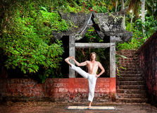 Yoga near temple. Yoga utthita hasta padangusthasana pose by man in white trousers near stone temple at sunset background in tropical forest Stock Photo