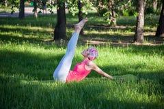 Yoga nel parco, all'aperto, salute del ` s delle donne, donna di yoga Il concetto dello stile di vita e della ricreazione sani gi Immagini Stock Libere da Diritti