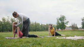 Yoga nel parco di mattina - l'istruttore sta formando le giovani donne per la flessibilità archivi video